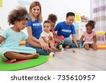 young volunteers playing with... | Shutterstock . vector #735610957
