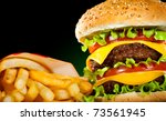 Tasty hamburger and french fries on a dark background - stock photo
