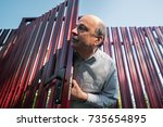 Small photo of Old caucasian man with mustache carefully watches and looks from behind the fence, opening door. He is suspecting something is wrong