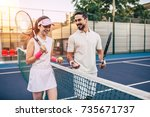young couple on tennis court.... | Shutterstock . vector #735671737