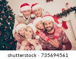 Small photo of Six beautiful caucasian relatives embrace, married couples, excited siblings, grandad, granny, in knitted cute traditional x mas costumes, pine firtree, home interior, stockings