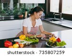 the young happy woman in apron...   Shutterstock . vector #735807259