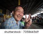 Small photo of Mea Klong Market, Thailand - October 9, 2017: Old toothless man smiling to camera at the Mea Klong Market train station