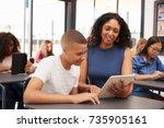 teacher helping teenage... | Shutterstock . vector #735905161