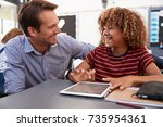 Small photo of Teacher and schoolboy with tablet looking at each other