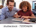 Small photo of Teacher and schoolboy using tablet computer in class