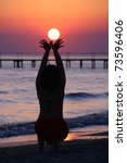 girl holds lowing sun at sunset. | Shutterstock . vector #73596406