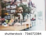 a man sitting in a cafe looking ... | Shutterstock . vector #736072384