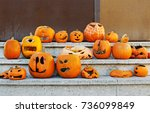 Small photo of Carved addled pumpkins are on stairs after Halloween