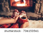 woman holding a cup of tea by... | Shutterstock . vector #736153561