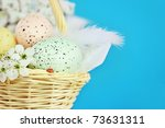 Basket full of Easter eggs in a basket with a ladybird and spring flowers against a blue background with room for copy space. Extreme shallow DOF. - stock photo
