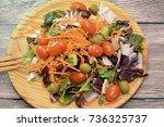 fresh salad on a wooden plate   Shutterstock . vector #736325737