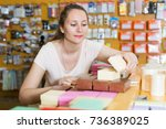 Small photo of Female emptor reviews gift boxes in the store