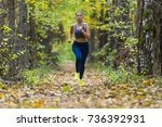 woman running in the autumn park | Shutterstock . vector #736392931