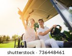 Happy Couple Riding A Golf Car...