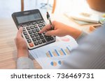 A businessman is calculating the revenue by using a calcultor.