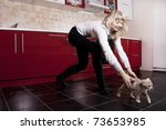 Stock photo young woman playing with a kitten on red kitchen 73653985