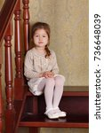 Small photo of Young brunette dolly lady girl stylish dressed in white skirt midi petticoat and cardigan strap shoes smiling posing sitting in studio on wooden stairs ladder with pout lips and pink cheeks