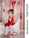 Small photo of Young brunette dolly lady girl stylish dressed in red dress strap shoes smiling posing sitting in studio and holding big huge heart with pout lips and pink cheeks