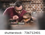 Small photo of Father teaching daughter to braze, concentrated process