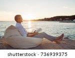 senior man reading a book lying ... | Shutterstock . vector #736939375