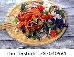 fresh salad on a wooden plate   Shutterstock . vector #737040961