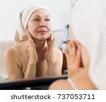 Small photo of Elderly woman using face cream during beauty procedures at home