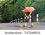 woman runner holding injured...   Shutterstock . vector #737269021