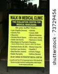 """VENICE BEACH, CA - MARCH 13: A sign for a local """"Walk In Medical Clinic"""" is shown on the Venice Beach Board Walk on March 13, 2011 in Venice Beach, CA - stock photo"""