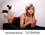 Small photo of Pretty young woman lying on black taboret with glass of wine