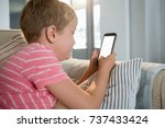 boy using mobile phone in the... | Shutterstock . vector #737433424