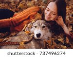 Stock photo young cute red haired girl walking with her dog in the park in a pile of fallen autumn leaves 737496274