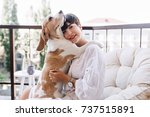 Small photo of Cute beagle dog hugging black-haired girl to express allegiance. Portrait of lovely young woman in white shirt and stylish accessories posing with pet on terrace in sunny day.