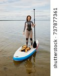 Small photo of Woman in suit stands with paddle in hand on inflatable SUP board.