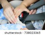 mother fastens her toddler... | Shutterstock . vector #738023365