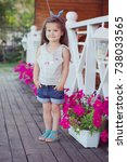 Small photo of Stylish beautifull cute baby girl with brunette hair posing on wooden garden full of flowers wearing tiny jeans shirts and airy skivy underwaist and blue sandals.