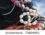 A pile of fishing nets and floats with a bright blue sky in the background - stock photo
