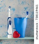 Small photo of Electric, and usual toothbrush in glass, small heart, on blue background