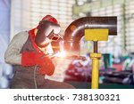 worker arc welding piping at... | Shutterstock . vector #738130321