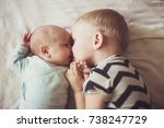 Small photo of older brother kisses younger brother