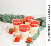 Small photo of Tasty strawberry dessert cheesecake trifle in glass on wooden table