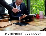 Small photo of Two businessman working on tablet, partner discuss plan or idea and opinion meeting, Asian bussinessman are discussing their working on a wood table beside window at coffee shop during breaking time