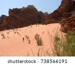 tourists hiking a dune in wadi... | Shutterstock . vector #738566191