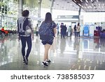 Small photo of Two asian young woman with backpack walking through to the departure area of the airport during their summer vacation.