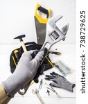 Small photo of close-up Allen wrench in hand with glove on the background of the bag with the tool