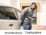 Young Hispanic man wearing a hoodie and trying to open a car door while no one watches - stock photo