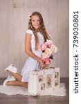 Small photo of Cute lady girl with blond hairs pink cheeks and blue eyes posing sit for camera in studio wearing airy white dress and fancy casuals pumps close to travelling trunk bag with pictures.