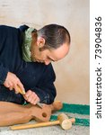 Sculptor Working On A Wooden...
