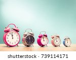Small photo of Five retro alarm clocks with last minutes to twelve o'clock on wooden table front gradient mint green wall background. Vintage old style filtered photo