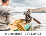 Stock photo happy couple canoeing in a lake in canada trees on background with colourful leaves during autumn 739115425